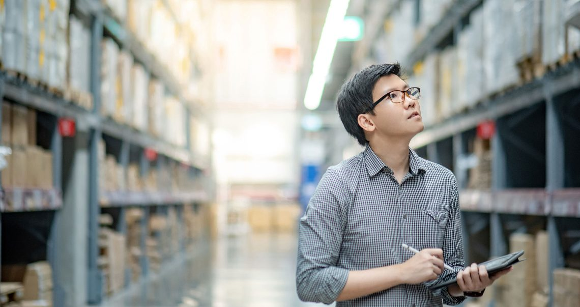 Asian manager man doing stocktaking of products in cardboard box on shelves in warehouse using digital tablet and pen. Male professional assistant checking stock in factory. Physical inventory count.; Shutterstock ID 1167283660; Other: ; Purchase Order: 123; Client/Licensee: ; Job: